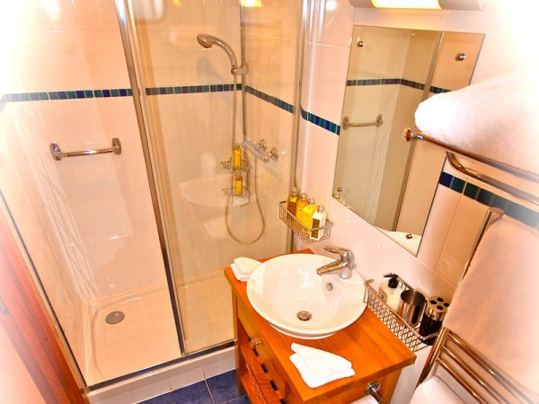 Roomy, modern ensuite bathrooms aboard the Apres Tout offer stand up showers<br> and heated towel racks