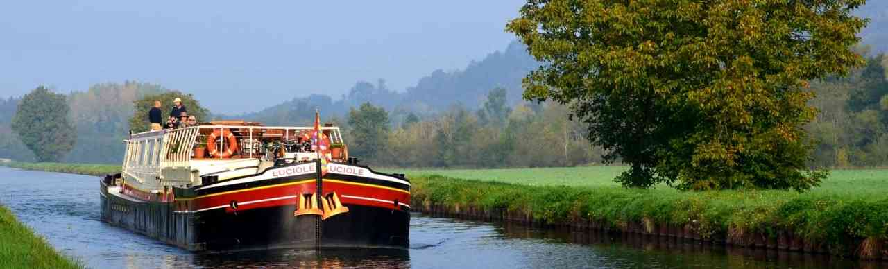 BargesInFrance.com: Master barge listing sorted by price per passenger, lowest to highest.  Pictured here is the 12-passenger barge Luciole, cruising on the Canal du Nivernais in the  Chablis wine region in Burgundy, France.