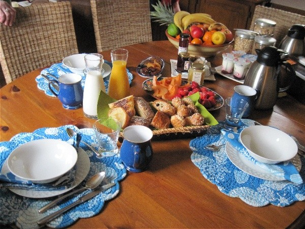 The breakfast table filled with delicious breads, croissants, fresh fruits and incredible assorted yogurts