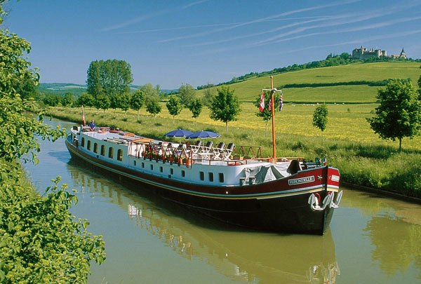 The Hirondelle cruising on the Burgundy Canal (Canal de Bourgogne) with the medieval village of Chateauneuf en Auxois on the hilltop.