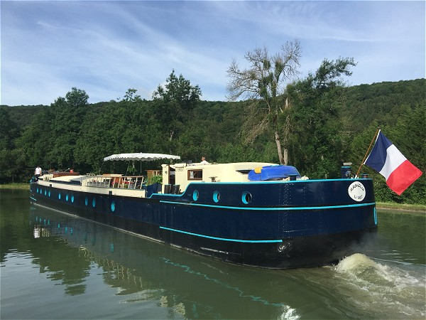 The 6-passenger Deluxe hotel barge Magnolia gently plys the waters of the Canal de Bourgogne.