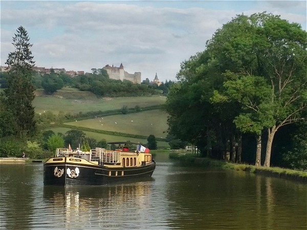 The 6-passenger Deluxe hotel barge Rendez-vous cruising on the beautiful Canal de Bourgogne,<br>beneath the picturesque and storied Chateauneuf en Auxois.