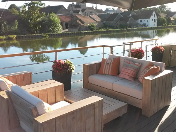 A lovely setee on the deck of the Rendez-vous; a great spot for a morning coffee<br>or a glass of wine, outside of a charming French village.