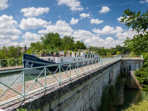 The Saint Louis cruising on an historic aqueduct over the River Baise