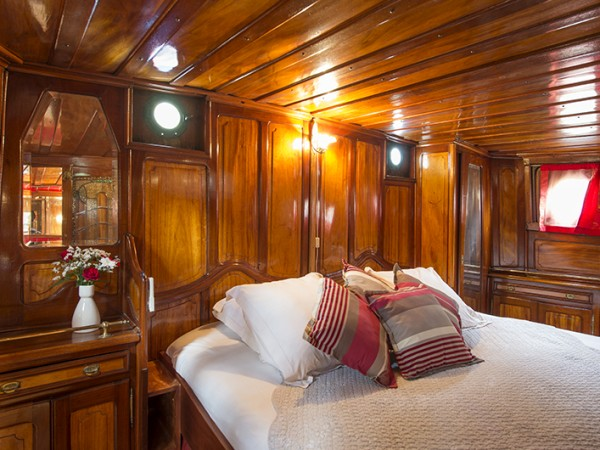 The Captain's cabin offers elegant dark wood and stained glass